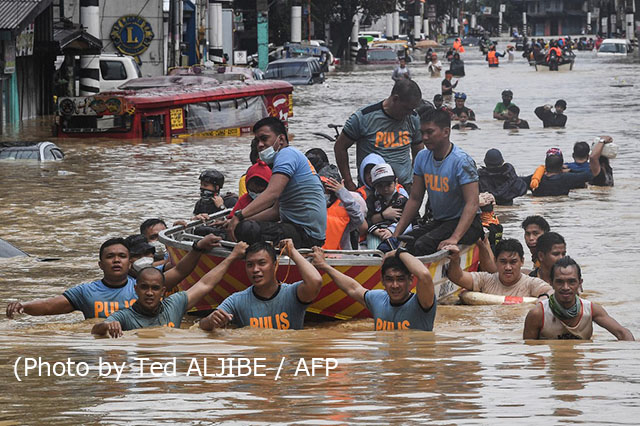 Rescuers pull a rubber boat carrying residents through a flooded street after Typhoon Vamco hit in Marikina City, suburban Manila on November 12, 2020. (Photo by Ted ALJIBE / AFP)